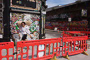 Person walking past roadworks and graffiti on a crossing in East London.