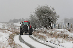 © Licensed to London News Pictures. 28/12/2020. Builth Wells, Powys, Wales, UK.  A tractor drives through a wintry landscape on the Mynydd Epynt moorland near Builth Wells in Powys, Wales, UK. Photo credit: Graham M. Lawrence/LNP