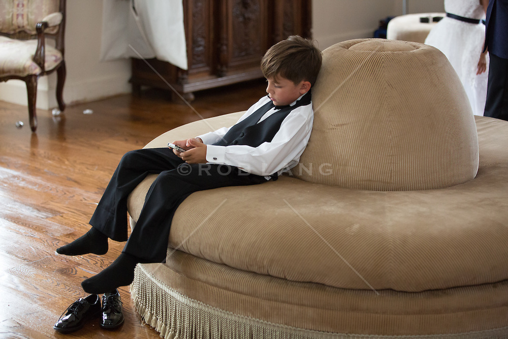 little boy at a wedding with his phone