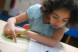 Young girl sitting at desk in classroom working on maths problem,