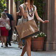 MILAN, ITALY - JULY 03:  A woman with a Gucci carrier bag walks  in the fashion district of Milan on the first day of the Summer Sales on July 3, 2010 in Milan, Italy. Milan's summer sales start today. .***Agreed Fee's Apply To All Image Use***.Marco Secchi /Xianpix. tel +44 (0) 207 1939846. e-mail ms@msecchi.com .www.marcosecchi.com