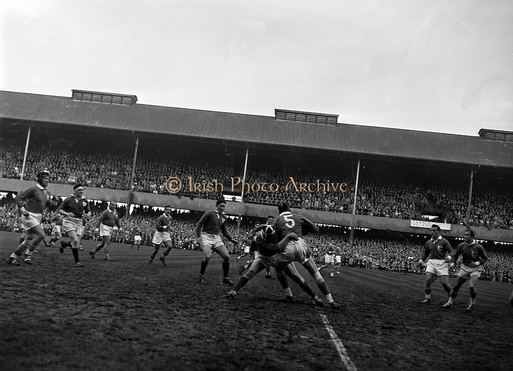 Culliton, Irish forward, tackles French forward Mommejat, while in possession of the ball, during the first half of the Ireland v France International Rugby match at Landsdowne Road, Dublin, on 18th April 1959,..Irish Rugby Football Union, Ireland v France, Five Nations, Landsdowne Road, Dublin, Ireland, Saturday 18th April, 1959,.18.4.1959, 4.18.1959,..Referee- D G Walters, Welsh Rugby Union, ..Score- Ireland 9 - 5 France, ..Irish Team, ..N J Henderson, Wearing number 15 Irish jersey, Full Back, N.I.F.C, Rugby Football Club, Belfast, Northern Ireland, ..A J O'Reilly, Wearing number 14 Irish jersey, Right Wing, Old Belvedere Rugby Football Club, Dublin, Ireland, and, Leicester Rugby Football Club, Leicester, England, ..M K Flynn, Wearing number 13 Irish jersey, Right Centre, Wanderers Rugby Football Club, Dublin, Ireland, ..D Hewitt, Wearing number 12 Irish jersey, Left centre, Queens University Rugby Football Club, Belfast, Northern Ireland,..N H Brophy, Wearing number 11 Irish jersey, Left wing, University College Dublin Rugby Football Club, Dublin, Ireland, ..M A F English, Wearing number 10 Irish jersey, Outside Half, Bohemians Rugby Football Club, Limerick, Ireland,..A A Mulligan, Wearing number 9 Irish jersey, Scrum Half, London Irish Rugby Football Club, Surrey, England, ..B G Wood, Wearing number 1 Irish jersey, Forward, Garryowen Rugby Football Club, Limerick, Ireland, ..A R Dawson, Wearing number 2 Irish jersey, Captain of the Irish team, Forward, Wanderers Rugby Football Club, Dublin, Ireland, ..S Millar, Wearing number 3 Irish jersey, Forward, Ballymena Rugby Football Club, Antrim, Northern Ireland,..W A Mulcahy, Wearing number 4 Irish jersey, Forward, University College Dublin Rugby Football Club, Dublin, Ireland, ..M G Culliton, Wearing number 5 Irish jersey, Forward, Wanderers Rugby Football Club, Dublin, Ireland, ..N Murphy, Wearing number 6 Irish jersey, Forward, Cork Constitution Rugby Football Club, Cork, Ireland,..P J A O' Sullivan, Wearing  Numb