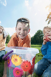Boy trying to take apple out of a bucket with their mouth, Munich, Bavaria, Germany