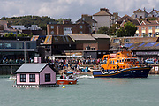 The Royal National Lifeboat Institution RNLI Dover Life boat 17-09 parked up next to a floating pink bungalow in Folkestone harbour built by the artist Richard Woods as part of the 2017 Folkestone Triennial  Folkestone, Kent. UK..