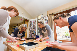 Hazel Griffiths, left, Susie Mullen, right and Jess Hayden make bread rolls with Baker Liz Wilson, who leads classes where participants learn a number of baking methods at her Fulham home in London. London, August 16 2019.