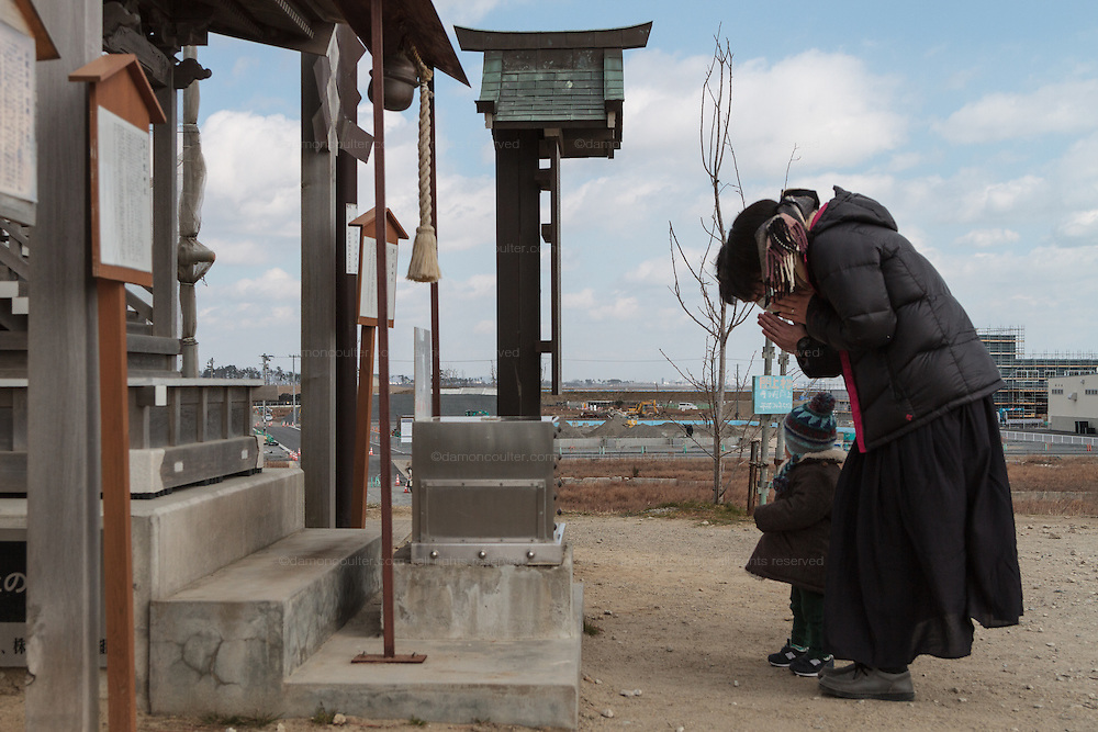 A family with a young child come to a shrine on Hiyori yama  or Weather Hill to remember victims of the tsunami at  Miyagi, Japan. Friday March 11th 2016. 2016 marks the fifth anniversary of the Great East Japan earthquake. This magnitude 9 quake caused a tsunami that flattened large parts of the Tohoku coast killing around 18,000 people and triggering a nuclear disaster at Fukushima Daichi Power Station.