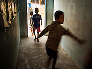 06 MARCH 2014 - MAE SOT, TAK, THAILAND: Students run through the hall after class at the Sky Blue School. There are approximately 140 students in the Sky Blue School, north of Mae Sot. The school is next to the main landfill for Mae Sot and serves the children of the people who work in the landfill. The school relies on grants and donations from Non Governmental Organizations (NGOs). Reforms in Myanmar have alllowed NGOs to operate in Myanmar, as a result many NGOs are shifting resources to operations in Myanmar, leaving Burmese migrants and refugees in Thailand vulnerable. The Sky Blue School was not able to pay its teachers for three months during the current school year because money promised by a NGO wasn't delivered when the NGO started to support schools in Burma. The school got an emergency grant from the Burma Migrant Teachers' Association and has since been able to pay the teachers.      PHOTO BY JACK KURTZ