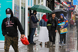 © Licensed to London News Pictures. 02/05/2021. London, UK. People are caught in the rain in north London. Windy and wet weather is forecasted for the bank holiday Monday.  Photo credit: Dinendra Haria/LNP