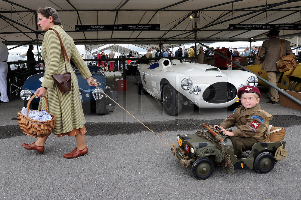 © Licensed to London News Pictures. 17/09/2011. GOODWOOD, UK. Karina Begood tows her son Thor aged 4 and a half past the garages lined with period cars. The Goodwood Revival at Goodwood in West Sussex today (17 September 2011). The revival is the world's largest historic motor race meeting, which relieves the 'glorious' days of the race circuit. Competitors and enthusiasts all dress in period fashion to enhance the experience. Photo credit : Stephen Simpson/LNP