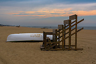 A life guard station turned on its side on the beach next to a lifeboat before the crowds arrive
