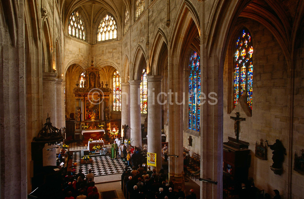 An aerial view of the rural Catholic church of Le Neubourg during the Sunday Mass for the local community. Local children help Father Phillipe Dubos, their parish priest conduct the Mass in front the rest of the congregation of parents and other regular churchgoers. Sunlight lights the beautiful stained glass windows and 16th century medieval columns and arches of Neubourg, Normandy. It is estimated that somewhere between 83% to 88% of France's population are Catholic. The church is organised into 98 dioceses, served by 20,523 priests.