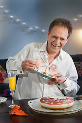 Mature man holding plate of cake accidentally spilt on shirt