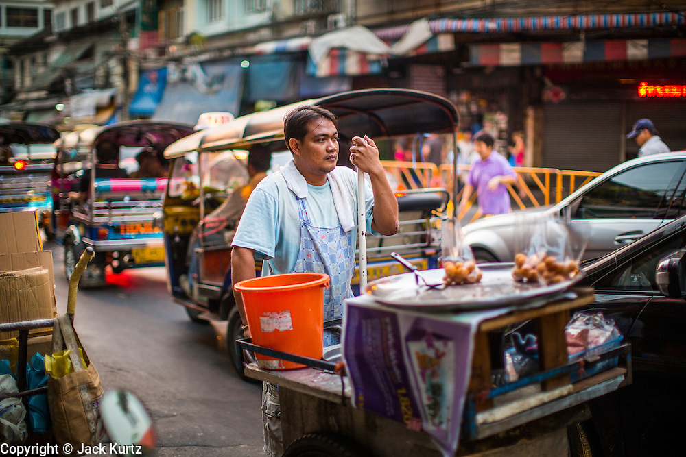 07 DECEMBER 2012 - BANGKOK, THAILAND:  A street food vendor pushes cart past tuk-tuks in the Chinatown section of Bangkok, Thailand. Chinatown is the entrepreneurial hub of Bangkok, with thousands of family owned businesses selling wholesale merchandise in everything from food like rice, peanuts and meats, to dry goods like toys and shoes. Tuk-tuks are three wheeled taxis that use a motorcycle engine. In one form or another they are common in much of Asia.     PHOTO BY JACK KURTZ