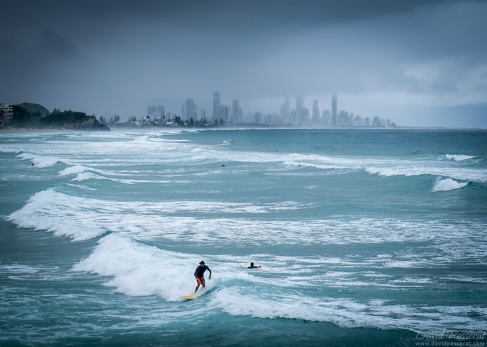 Surfing on a cloudy day in Robina. The city of Brisbane on the Est coast of Australia can be seen in the background
