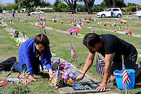 Debra and Ben Parcasio, Jr. clean family graves at Garden of Memories Memorial Park on Monday in Salinas. Ben Parcasio, a WWII and Korean War veteran and survivor of the Bataan Death March, died in 1997 - his wife, Cipriana Quirante, in 2009.