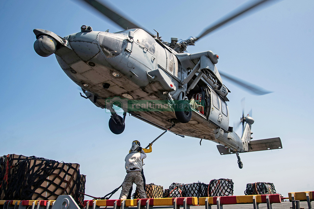"""180930-N-RP442-2324<br /> ARABIAN GULF (Sept. 30, 2018) An MH-60S Sea Hawk helicopter, assigned to the """"Blackjacks"""" of Helicopter Sea Combat Squadron (HSC) 21, prepares to transport cargo from the flight deck of the Wasp-Class amphibious assault ship USS Essex (LHD 2) while participating in a vertical replenishment during a scheduled deployment with the Essex Amphibious Ready Group (ARG) and 13th Marine Expeditionary Unit (MEU). The Essex is a lethal, flexible, and persistent Navy-Marine Corps team deployed to the U.S 5th Fleet area of operation in support of naval operations to ensure maritime stability and security in the Central Region, connecting the Mediterranean and the Pacific through the western Indian Ocean and three strategic choke points. (U.S Navy photo by Mass Communication Specialist 3rd Class Jenna Dobson/Released)"""