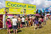 People line up in front of the Coconut Man stall in the main arena for fresh coconut water. WOMAD 2014, festival of world music and dance, Charlton Park, Wiltshire. UK.