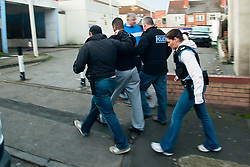 After a forced entry using a chainsaw South Yorkshire Police Officers escort a man away in handcuffs from an address in Eastwood Rotherham early on Tuesday Morning<br /> <br /> 04 March 2014<br /> Image © Paul David Drabble <br /> <br /> www.pauldaviddrabble.co.uk