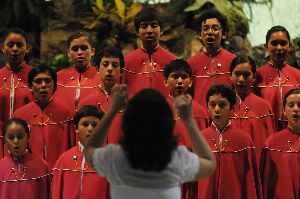 Choir Conductor Elizabeth Espejal Cruz (back to camera) leads Niños Cantores de Morelia before a packed audience at St. Gall Parish on Chicago's southwest side.