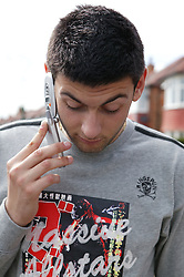 Young man walking outside using a mobile telephone; model released for use in HIV and Aids,