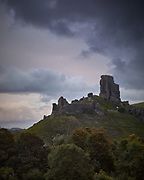 The ruins of Corfe Castle silhouetted against the last light at the moment storm clouds arrive overhead. Storm Alex, 1st October 2020.
