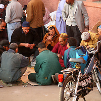 North Africa, Africa, Morocco.  A group of Moroccan men gather to play games and pass time.