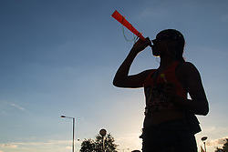 London, August 29th 2016. As the sun sets a woman blows a horn at the end of day two of Europe's biggest street party, the Notting Hill Carnival.