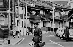 District 6-D23.jpg<br /> Lunchbox and Argus in hand, a worker returns home to District Six.