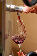 Domaine Mas Cal Demoura, in Jonquieres village. Terrasses de Larzac. Languedoc. Pouring a wine sample in a glass. Stainless steel fermentation and storage tanks. Tank spout. Owner winemaker. France. Europe.