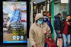© Licensed to London News Pictures. 19/12/2020. London, UK. A man wearing a face covering in north London walks past the government's COVID-19 publicity campaign poster amid fears of a Christmas lockdown as infection rates rise. Prime Minister Boris Johnson will hold a press conference later today after meeting with ministers, where it is understood they discussed a possible ban on commuters entering London and travel to and from the South East. Photo credit: Dinendra Haria/LNP