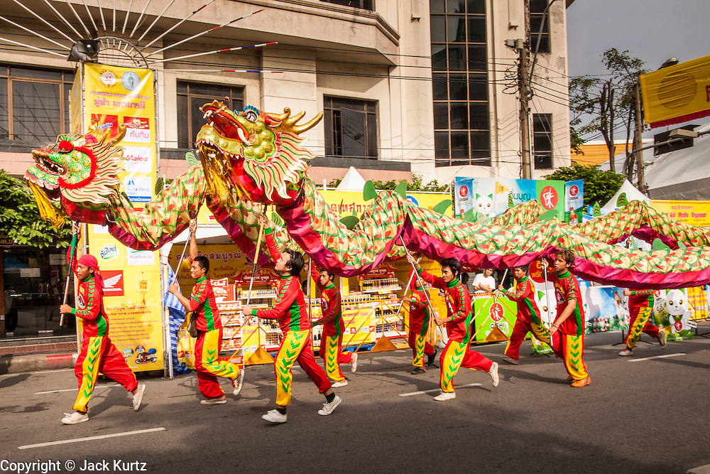 14 OCTOBER 2012 - BANGKOK, THAILAND:  A team of dancers perform during a procession to a shrine on Yaowarat Road on the first day of the Vegetarian Festival in Bangkok's Chinatown. The Vegetarian Festival is celebrated throughout Thailand. It is the Thai version of the The Nine Emperor Gods Festival, a nine-day Taoist celebration beginning on the eve of 9th lunar month of the Chinese calendar. During a period of nine days, those who are participating in the festival dress all in white and abstain from eating meat, poultry, seafood, and dairy products. Vendors and proprietors of restaurants indicate that vegetarian food is for sale by putting a yellow flag out with Thai characters for meatless written on it in red.     PHOTO BY JACK KURTZ
