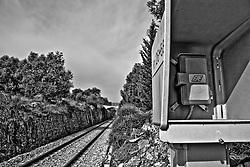 in fondo al binario che collega le stazioni del salento denominate FSE si intravede un ponte che collega i due costoni di roccia che costituiscono le pareti del tunnel scavato per costuire la ferrovia. Reportage che racconta le situazioni che si incontrano durante il viaggio lungo le linee ferroviarie SUD EST nel Salento.