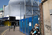 Woman wearing a surgical face mask near the iconic Selfridges building on 24th April 2020 in Birmingham, England, United Kingdom. Coronavirus or Covid-19 is a new respiratory illness that has not previously been seen in humans. While much or Europe has been placed into lockdown, the UK government has extended stringent rules as part of their long term strategy, and in particular social distancing.