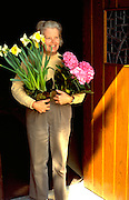 Woman age 66 holding flowers for Easter Service.  WesternSprings  Illinois USA