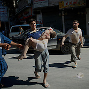 August 10, 2012 - Aleppo, Syria: A young man carries his brother, seriously injured minutes earlier by heavy shelling from the Syrian Army against a bakery in the residential area of Tariq Al-Bab in central Aleppo. At least 12 people have died and more the 20 got injured during the attack...The Syrian Army have in the past week increased their attacks on residential neighborhoods where Free Syria Army rebel fights have their positions in Syria's commercial capital, Aleppo.