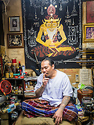 """25 MAY 2015 - BANGKOK, THAILAND:  AJARN NENG ONNUT (also known as Khun Pean) in his Sak Yant tattoo parlor. Sak Yant (Thai for """"tattoos of mystical drawings"""" sak=tattoo, yantra=mystical drawing) tattoos are popular throughout Thailand, Cambodia, Laos and Myanmar. The tattoos are believed to impart magical powers to the people who have them. People get the tattoos to address specific needs. For example, a business person would get a tattoo to make his business successful, and a soldier would get a tattoo to help him in battle. The tattoos are blessed by monks or people who have magical powers. Ajarn Neng, a revered tattoo master in Bangkok, uses stainless steel needles to tattoo, other tattoo masters use bamboo needles. The tattoos are growing in popularity with tourists, but Thai religious leaders try to discourage tattoo masters from giving tourists tattoos for ornamental reasons.       PHOTO BY JACK KURTZ"""