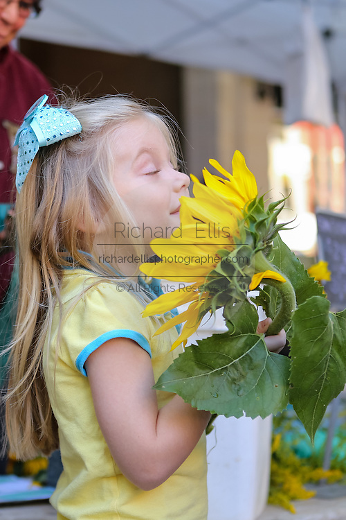 A little girl smells a sunflower at the Farmers Market along Main Street in downtown Greenville, South Carolina.