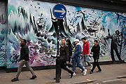 People interact with large scale street art graffiti artwork depicting wild seas and crashing waves on Berwick Street in Soho on 18th February 2020 in London, England, United Kingdom. Part of Soho's ex-red light district, Berwick Street is one of central London's most varied thoroughfares full of small independent shops.