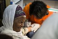 Una pellegrina etiope soffre mentre Wassim gli tatua il braccio