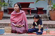 """Mar. 15, 2009 -- LUANG PRABANG, LAOS:  A woman and her daughter wait for Buddhist Monks in Luang Prabang, Laos, who are on their """"Tak Bat,"""" Lao for """"monks morning rounds."""" The monks collect alms in the form of food from people who line their route. For the monks, it is the only food they get that day, for the people it's a chance to """"make merit."""" Luang Prabang is a UNESCO World Heritage Site and the spiritual capital of Laos. There are dozens of """"wats"""" or temples and thousands of monks in the city. It is still the center of Buddhist education in Laos. Photo by Jack Kurtz / ZUMA Press"""