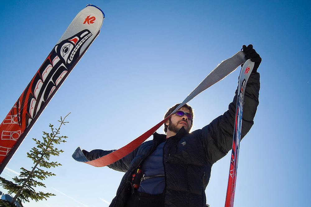 Nick Cowan removes climbing skins from his skis on Heather Ridge, Stevens Pass, Washington.