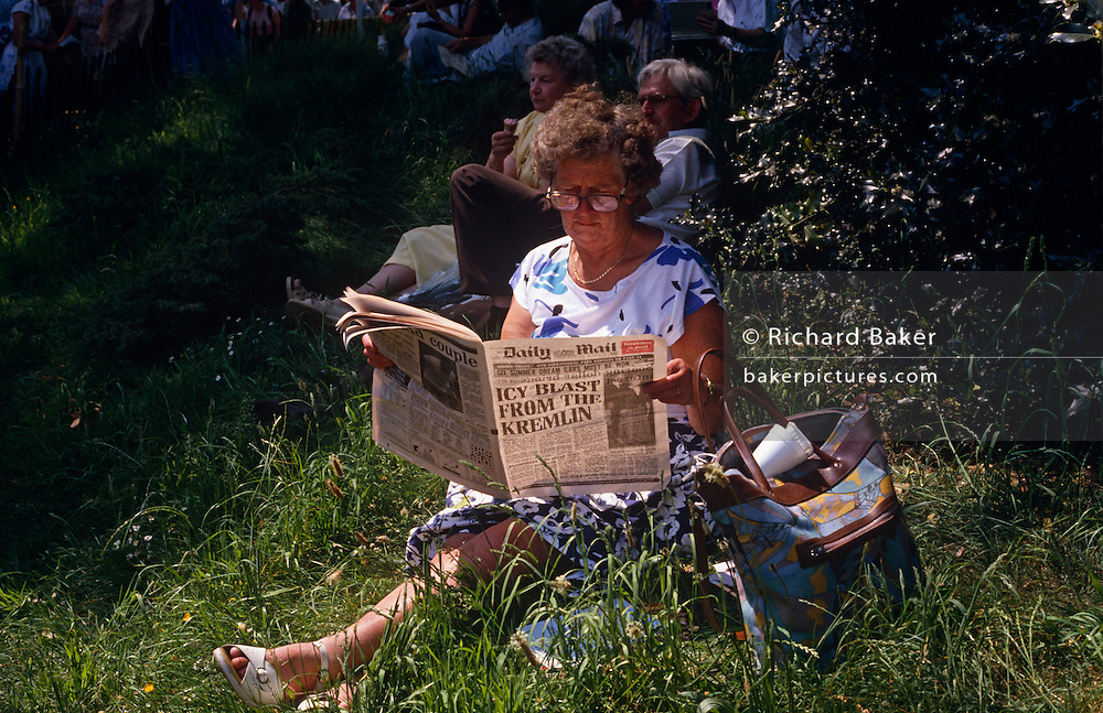 Sitting among others in long grass a middle-class lady reads the high-circulation Daily Mail newspaper during a lunchtime break at the Chelsea Flower Show, in London England. The front page headline reads 'Icy Blast from the Kremlin' in an echo from the darkest days of the Cold War, when western media fuelled the insatiable appetite for propaganda. But this scene is from May 1989 before the fall of the Berlin Wall and when the eastern states of the Warsaw Pact were still ruled by their Communist masters. Visitors to this annual horticultural event either sit in the cool shade or like this woman who appears comfortable cross-legged in sandals and a summer dress, stays under the hot mid-day sun with her tabloid format paper spread and with her possessions kept in a shoulder bag.