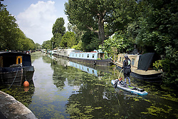 © Licensed to London News Pictures. 02/07/2021. London, UK. A woman relaxes on a paddle board as she passes along the canal at Little Venice in west London on a warm summer's day. Photo credit: Ben Cawthra/LNP