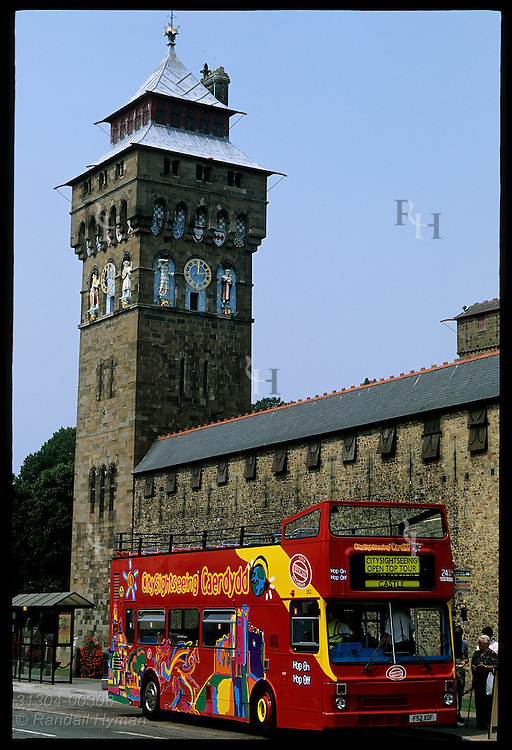 Clock tower looms over tour bus and 19th-C wall built atop original Roman ruins by Lord Bute at Cardiff Castle; Cardiff, Wales.