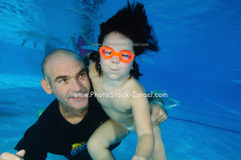 Father and three year old child swim underwater in a pool
