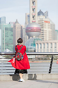 Tourist looking at the futuristic cityscape of Lujiazui skyline from the Bund, Shanghai, China