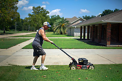 28 August 2014. Braithwaite, Louisiana.<br /> Hurricane Isaac 2 years later. <br /> Keeping up appearances.  Russell Gelvin cuts the grass. The predominantly white middle class neighborhood of Braithwaite Park, established in 1936 remains  abandoned as residents failed to return following the flooding and subsequent chemical spill from nearby Stolthaven chemical storage facility.  Insurance companies have often refused to pay residents the full value on their policies and many are now in litigation. Houses once valued at well over $250,000 are rapidly falling into disrepair and blight. Parish ordinances require owners of the abandoned homes to maintain the empty properties. Hurricane Isaac hit on August 29th, 2012.<br /> Photo; Charlie Varley
