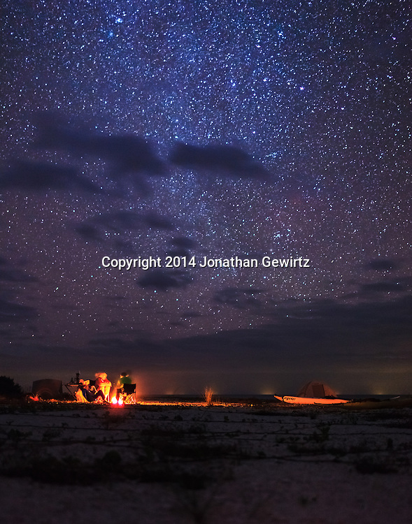 Campers sit around a fire under a magnificent starry night sky on the beach at East Cape Sable, on Florida Bay at the southern end of Everglades National Park. WATERMARKS WILL NOT APPEAR ON PRINTS OR LICENSED IMAGES.