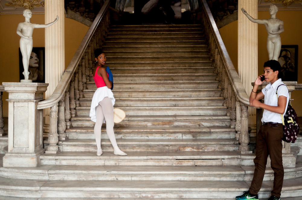 A Cuban dancer looks on in the dance hall while her boyfriend talks on a smartphone.