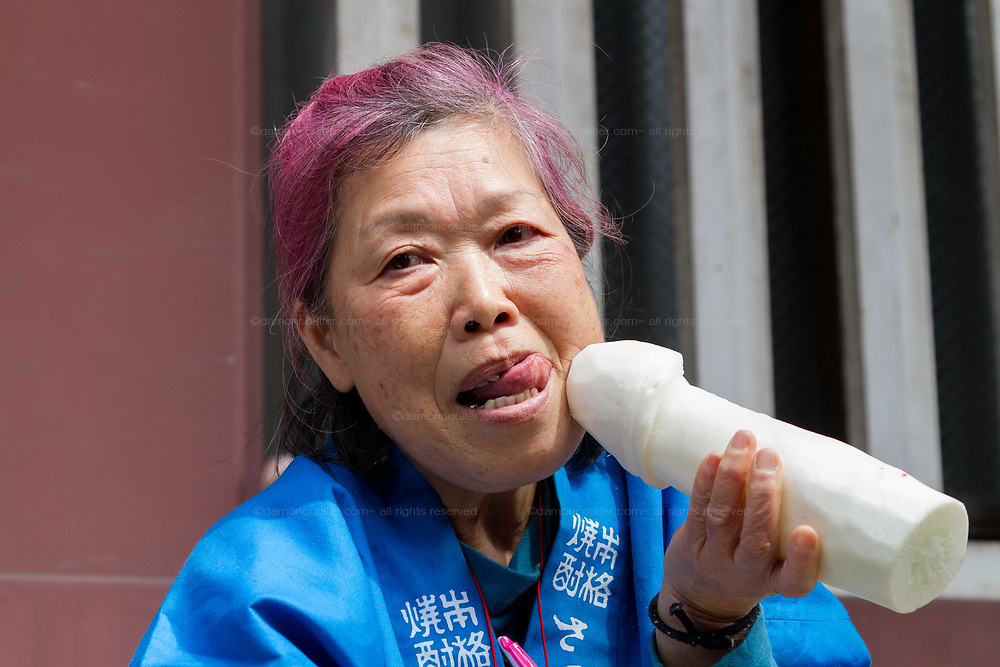 An older Japanese woman poses with a white radish carved in to the shape of a penis at the Kanamara matsuri or festival of the Steel phallus Kawasaki Daishi, Kawasaki, Kanagawa, Japan. Sunday, April 2nd 2017. The Kanamara Penis festival takes place on the first Sunday of April and celebrates the local legend of a penis eating demon who was defeated after being tricked into biting a steel phallus. The festival is popular with Japan's gay community and now uses its notoriety to raise money for HIV and AIDS charities. It is also wildly popular with foreign and Japanese.tourists.